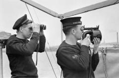 L5 A_British_sailor_signalling_by_hand_held_flash_lamp_aboard_the_Dutch_Torpedo_Boat_Z_5_as_it_serves_with_the_British_Fleet._His_dutch_shipmate_is_looking_out_for_the_reply_through_a_pair_of_binoculars,_1941._A3983