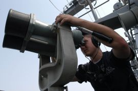 R1 US_Navy_050718-N-7647G-011_Seaman_Ryan_Henderson_looks_through_the_Big_Eyes_binoculars_while_searching_for_surface_and_air_contacts_during_an_aft_look_out_watch_aboard_the_nuclear-powered_aircraft_carrier_USS_Nimitz_(CVN_68)